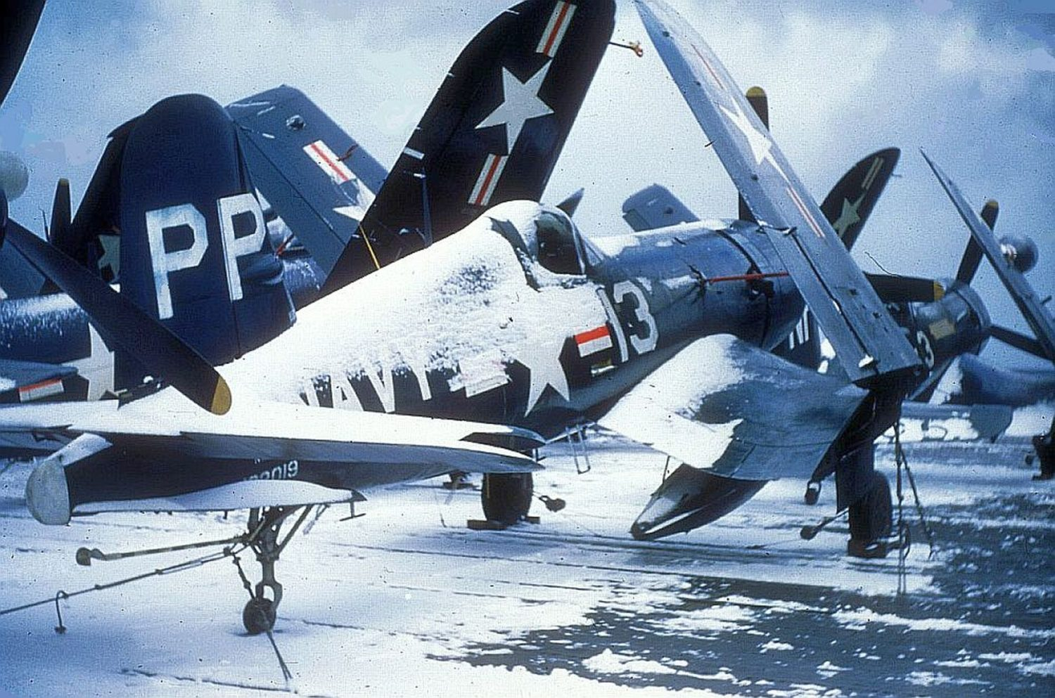 A snow covered VC-61 Vought F4U-4P with a VC-3 F4U-5N Corsair forward on a CV during the winter of 1950-51 in Korean waters. Tailhook Association